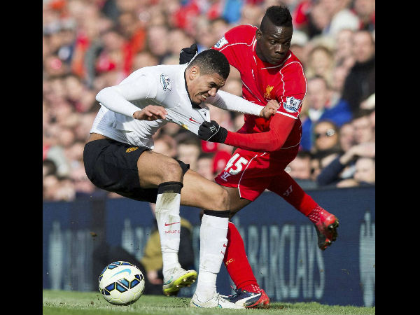 Liverpool's Mario Balotelli, right, fights for the ball against Manchester United's Chris Smalling during the English Premier League soccer match between Liverpool and Manchester United.