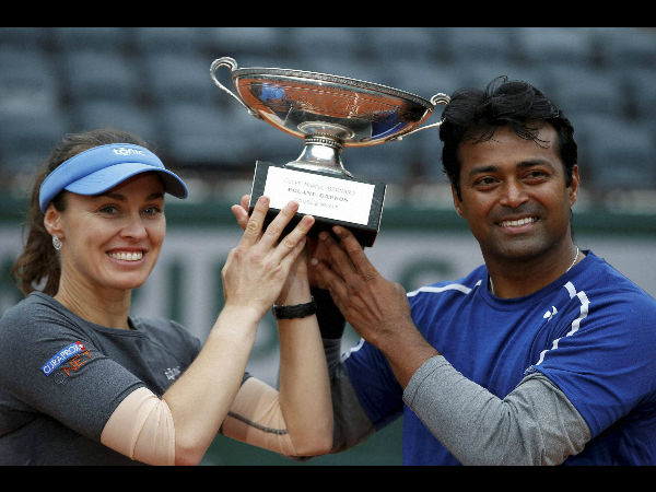 Switzerland's Martina Hingis, left, and India's Leander Paes hold the trophy after winning the mixed doubles final of the French Open tennis tournament against India's Sania Mirza and Croatia's Ivan Dodic at the Roland Garros stadium in Paris, France, Friday, June 3, 2016.