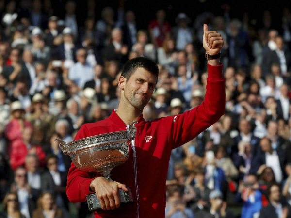 Serbia's Novak Djokovic gives a thumbs up as he holds the trophy after winning the final of the French Open tennis tournament.