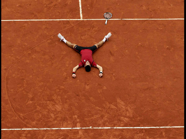 Serbia's Novak Djokovic lays on the clay in a heart in drew after defeating Britain's Andy Murray during their final match of the French Open tennis tournament at the Roland Garros.
