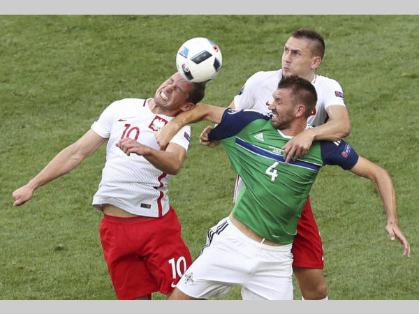 Poland's Grzegorz Krychowiak, left, and Artur Jedrzejczyk, right, go for a header with Northern Ireland's Gareth McAuley during the Euro 2016 Group C match