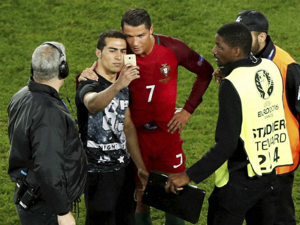 Portugal's Cristiano Ronaldo joins pitch invader for selfie