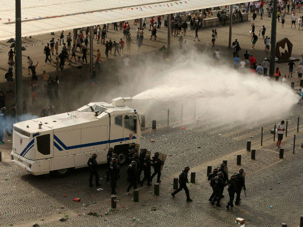 Police fire water cannons to control the fighting fter football fans clashed ahead of the England v Russia Euro 2016 soccer match, in Marseille, France, Saturday June 11, 2016.