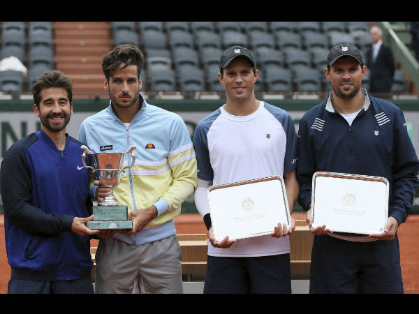 Spanish pair Feliciano Lopez, second left,, and Marc Lopez, left, hold their trophy after winning the men's doubles final match of the French Open tennis tournament against Bob, right, and Mike Bryan, of the U.S, at the Roland Garros stadium, Saturday, June 4, 2016 in Paris.