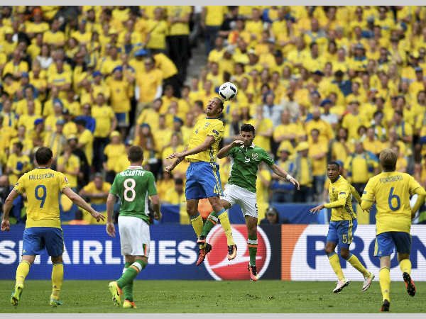 Sweden's Andreas Granqvist, center left, jumps for the ball with Ireland's Shane Long during the Euro 2016 Group E match