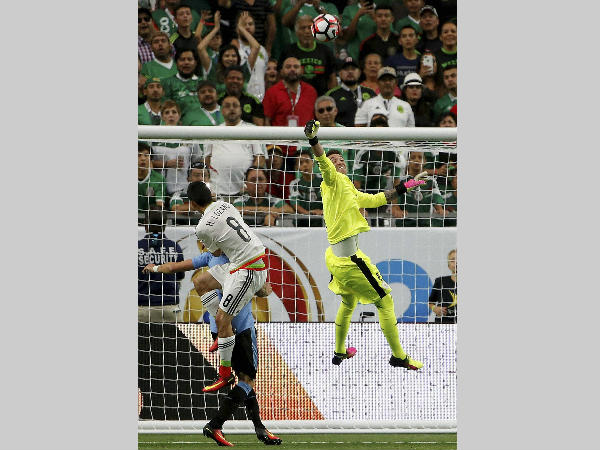 Uruguay's Fernando Muslera, right, makes a save on a shot by Mexico's Hirving Lozano (8) during the second half of a Copa America group C soccer match at University of Phoenix Stadium