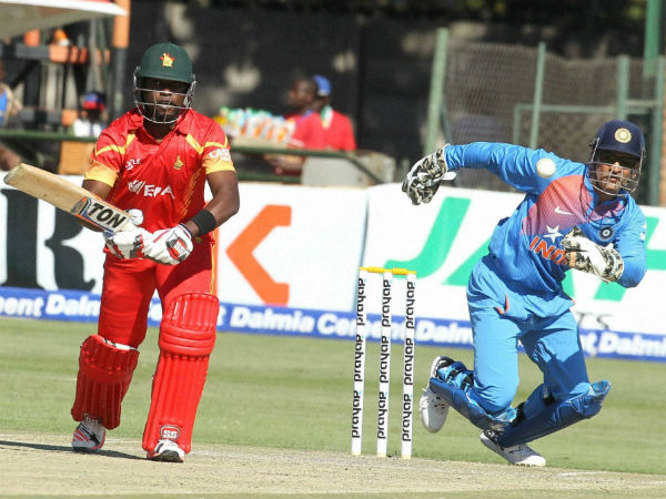 Zimbabwe's Elton Chigumbura, left, plays a shot as Indian wicketkeeper MS Dhoni fields, during the T20 International cricket match between Zimbabwe and India at Harare Sports Club, on June, 18, 2016.