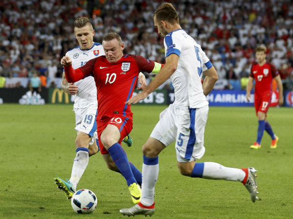 England's Wayne Rooney, center, is challenged by Slovakia's Juraj Kucka, left, and Norbert Gyomber, during the Euro 2016 Group B soccer match between Slovakia and England.