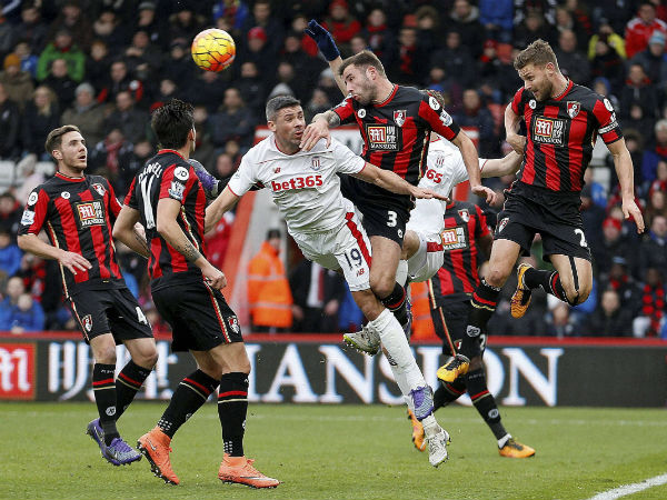 AFC Bournemouth's Simon Francis, right, and Steve Cook, second right battle for the ball with Stoke City's Jonathan Walters during the English Premier League soccer match at the Vitality Stadium, Bournemouth, England.