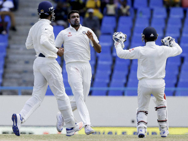 Ashwin (centre) celebrates with team-mates after taking a wicket against West Indies in the 1st Test