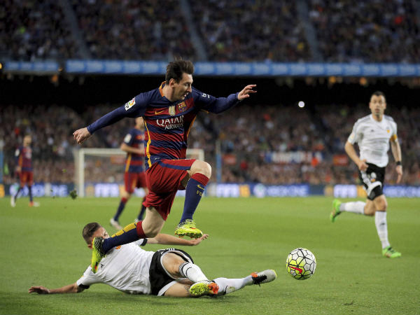 FC Barcelona's Lionel Messi, second left, duels for the ball against Valencia's Guilherme Siqueira during a Spanish La Liga match