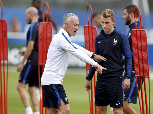 Didier Deschamps (left) talks to player Lucas Digne, right, during a training session of the national soccer team of France