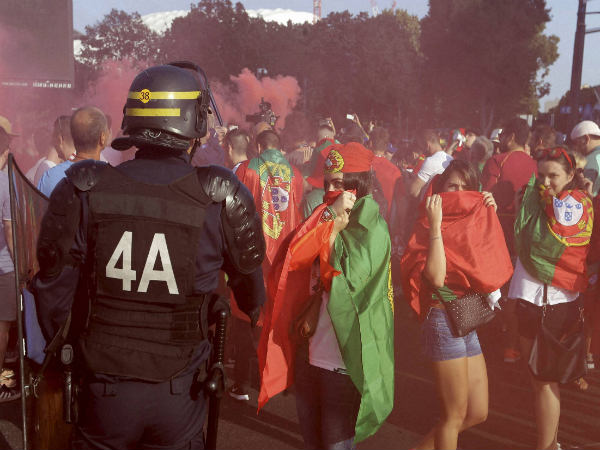 Portugal supporters cover their faces as other fans hold flares prior the Euro 2016 quarterfinal match between Poland and Portugal