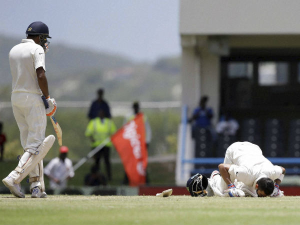 India's Ravichandran Ashwin, left, walks towards his captain Virat Kohli as he kisses the field after scoring a double-century during day two of the first cricket Test match against West Indies.