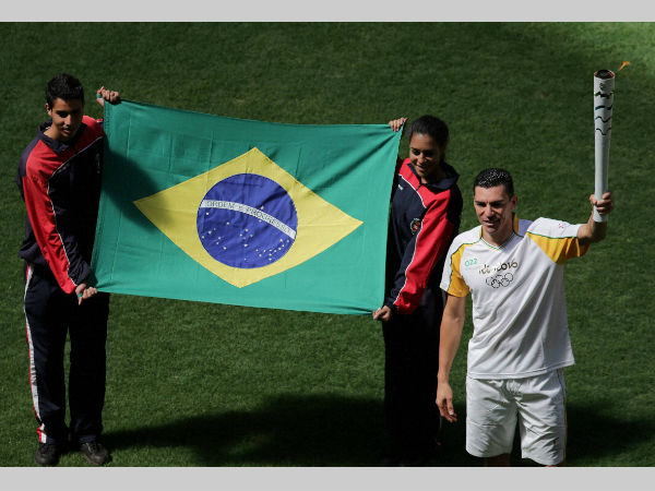 File photo: Brazil's former soccer player Lucio da Silva Ferreira holds the Olympic torch by the Brazilian flag during the torch relay in Brasilia in May.