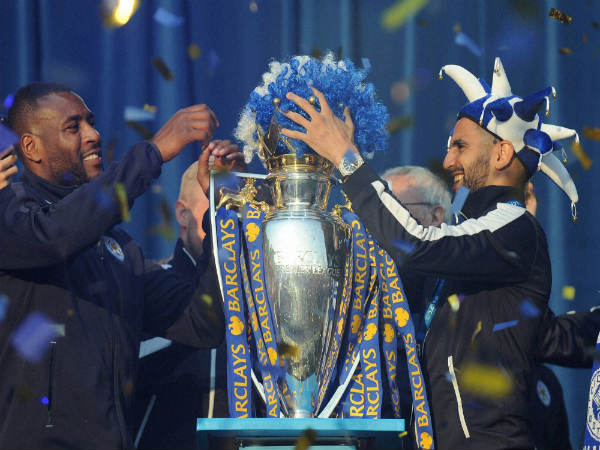 Leicester's Riyad Mahrez (right) place a Leicester wig in club colours on the Premier League Trophy