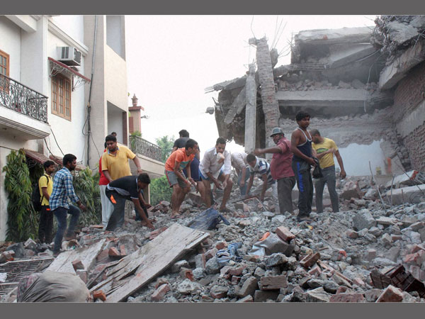 Local people engaging in rescue works after a building collapsed during an anti-encroachment drive in Meerut Cantonment area in Meerut