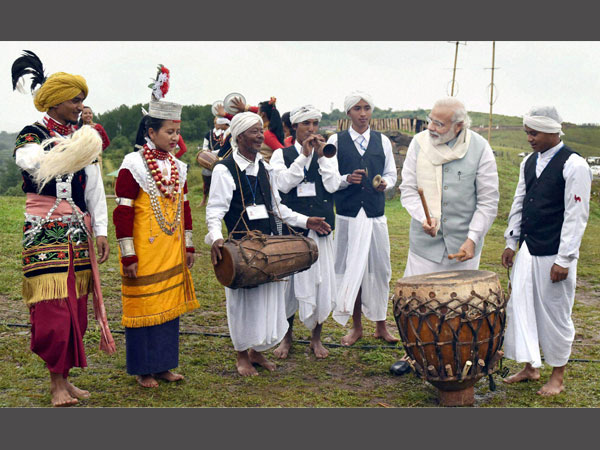 PM Narendra Modi with artists tries his hands at a drum in Heritage Mawphlang village in Meghalaya.