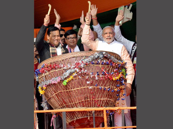 PM Narendra Modi, along with Union Minister and Assam BJP state president Sarbananda Sonowal beats a 'Maadol', the traditional drum of tea tribes, during a public rally at Moran in Dibrugarh district of Assam.