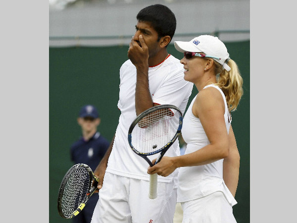 Rohan Bopanna talks to playing partner Anastasia Rodionova of Australia during their mixed doubles match against Juan-Sebastian Cabal and Maraiana Duque-Marino of Colombia