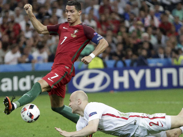 Cristiano Ronaldo, left, tries to control the ball near Poland's Michal Pazdan during the Euro 2016 quarterfinal soccer match between Poland and Portugal