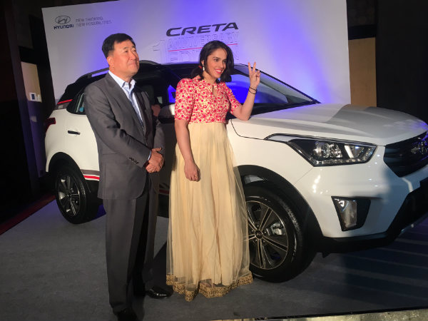 Saina poses with her SUV Creta, which was handed over to her by Hyundai Motor India MD and CEO Koo (left) in Bengaluru. Photo by Suhas A