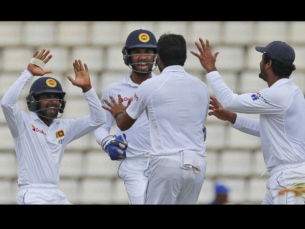Sri Lankan team members celebrate the dismissal of Australia's Usman Khawaja with their bowler Dilruwan Perera, second right, on day four of the first test cricket match between Sri Lanka and Australia in Pallekele.