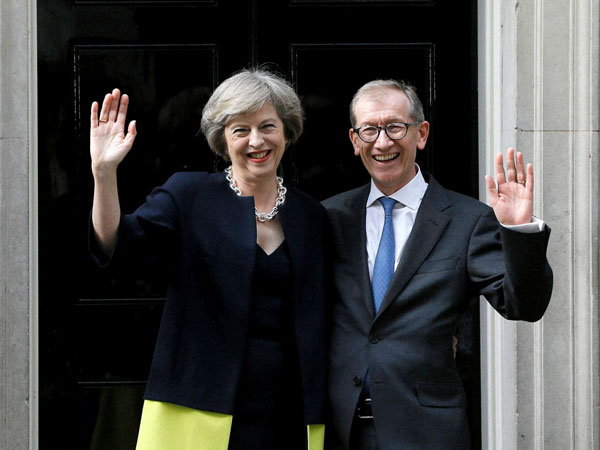 New British Prime Minister Theresa May and her husband Philip May wave from the steps of 10 Downing Street in London.