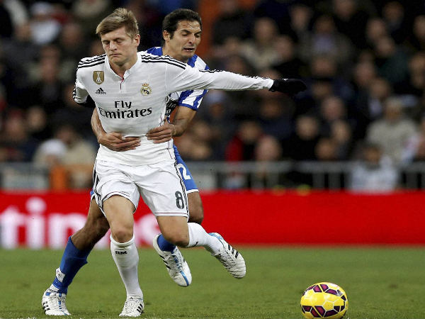 Toni Kroos (left) is grabbed by Celso Borges while they duel for the ball during a match between Real Madrid and Deportivo La Coruna