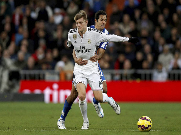 Real Madrid's Toni Kroos f(left) is grabbed by Celso Borges while they duel for the ball during a Spanish La Liga match last season