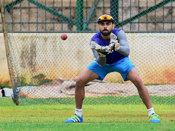 A watchful Virat Kohli gets ready to take a catch with big gloves at the NCA on Friday (July 1)