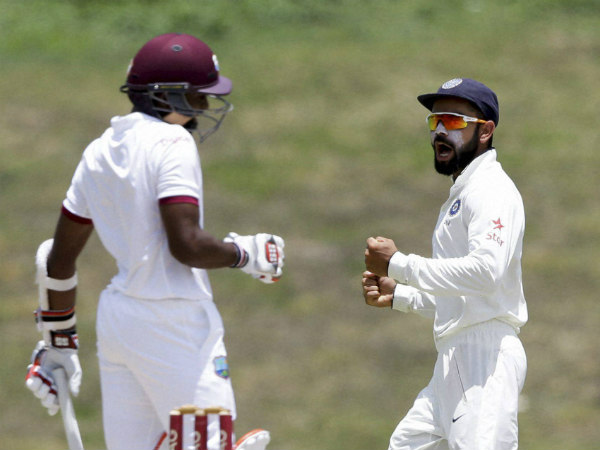 Kohli (right) celebrates a wicket during the 1st Test against West Indies in North Sound, Antigua