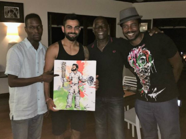 Vivian Richards (second right) and his son Mali (left) gift Virat Kohli (second left) a painting. Mali's business partner Ron Howell (Guava De Artist) is also seen. Photo from BCCI's Twitter page