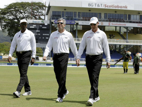 Umpires Nigel Llong, center, Gregory Brathwaite, left, and Rod Tucker inspect inspect the field as a wet ground delays the start of day two of the fourth cricket Test match between India and West Indies at Queen's Park Oval in Port-of-Spain.