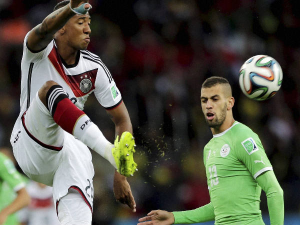 Jerome Boateng (left) clears a ball while defending against Algeria
