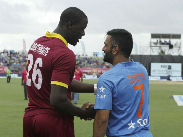 West Indies' Carlos Brathwaite (26) shakes hands with India's MS Dhoni (7) after the second Twenty20 international cricket match was called off due to rain, Sunday, Aug. 28, 2016, in Lauderhill