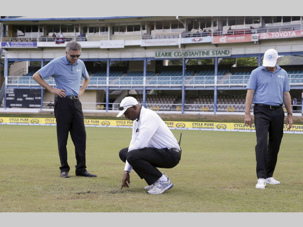 Umpires Nigel Llong, left, Gregory Brathwaite, centre, and Rod Tucker inspect the field as a wet ground delays the start of day three of the 4th Test