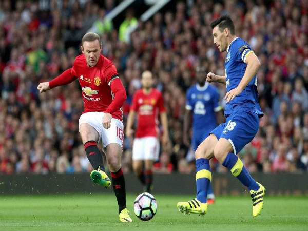 Wayne Rooney (left) in action against Everton