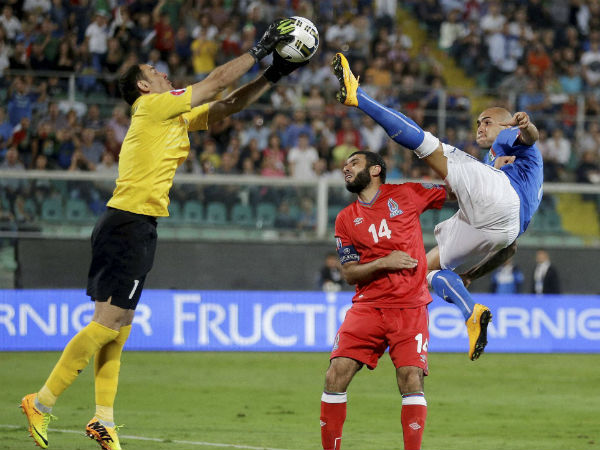 Italy's Simone Zaza, right, vies for the ball with Azerbaijan goalkeeper Kamran Agayev, left, as Azerbaijan's Rashad Sadygov tries to stop him during the Euro 2016 qualifying soccer match between Italy and Azerbaijan, at the La Favorita stadium, in Palermo, Italy, Friday, Oct. 10, 2014.