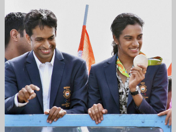 Gopichand (left) and Sindhu in Hyderabad on Monday after returning home from Rio Olympics. Sindhu shows her silver medal to the fans who had gathered to welcome her