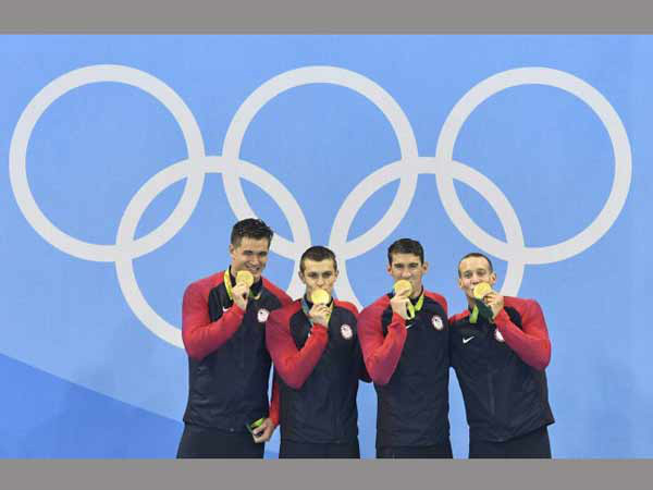 From right United States' Caeleb Dressel, Michael Phelps, Ryan Held, and Nathan Adrian, celebrate in the medals ceremony after winning gold