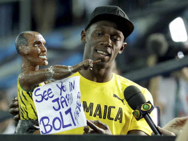 Usain Bolt holds a model of himself as he celebrates winning the gold medal in the men's 4x100-metre relay at Rio Olympics