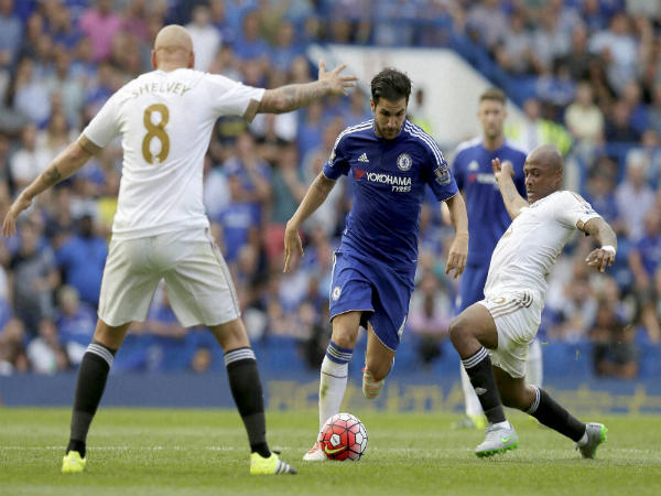 Cesc Fabregas (blue) in action against Swansea City