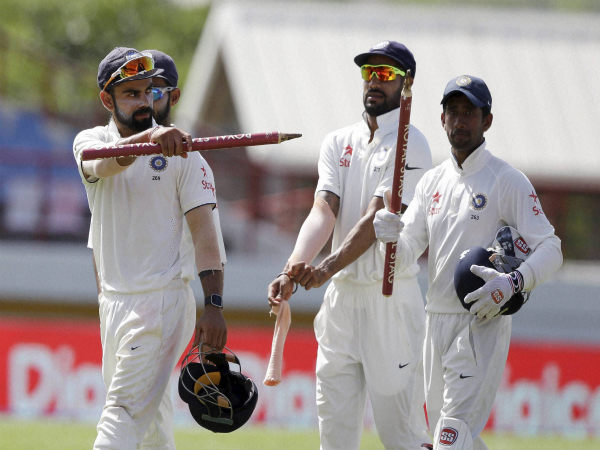India's captain Virat Kohli (left) shows the wicket as he leaves the field with wicketkeeper Wriddhiman Saha (right) and Shikhar Dhawan after defeating West Indies
