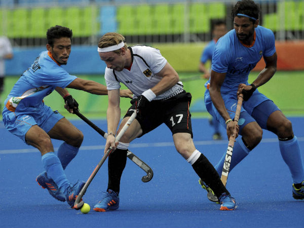 Germany's Christopher Rhur, center, fight for the ball against India's Kothajit Khadangbam, left, and India's Rupinder Pal Singh, right, during a men's field hockey match at 2016 Summer Olympics in Rio de Janeiro, Brazil, Monday, Aug. 8, 2016.