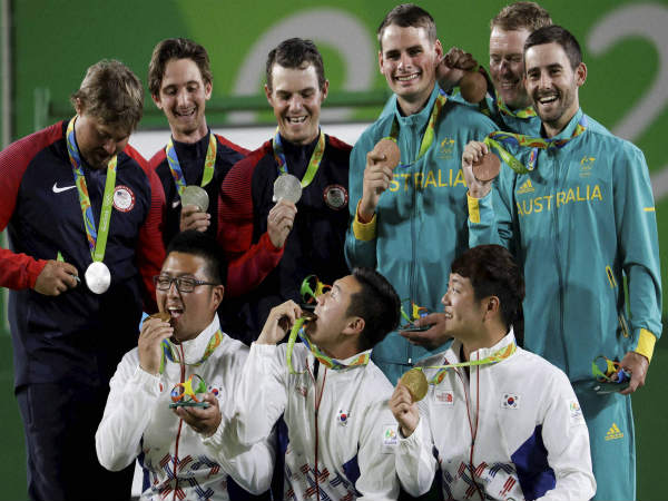 Gold medalists from South Korea (bottom) celebrate their triumph in men's archery