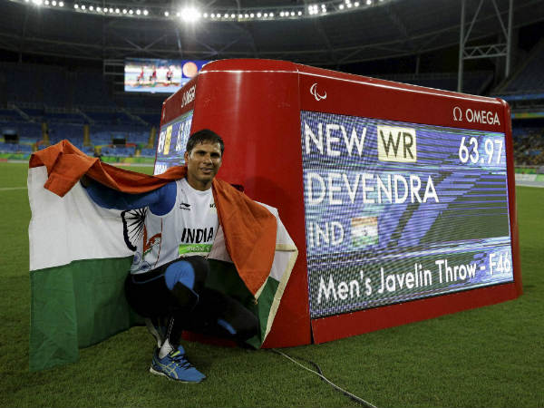 India's Devendra Jhajharia poses for the pictures next to the scoreboard that shows his world record in the men's javelin throw F46 athletics event at the Paralympic Games in Rio de Janeiro