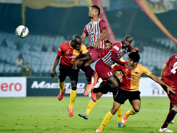 East Bengal (red and yellow) and Mohun Bagan (green and maroon) players fight for the ball