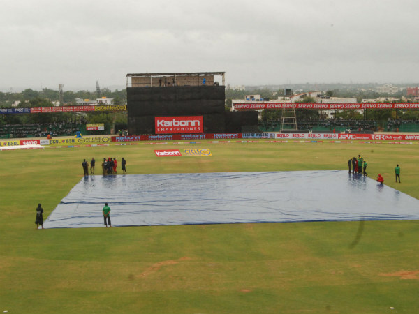 KSCA Stadium's pitch is covered as rain stops play