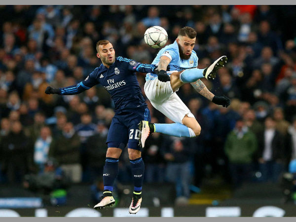 Real Madrid's Rodriguez Jese and Manchester City's Nicolas Otamendi, right, battle for the ball during the Champions League semifinal soccer match at the Etihad Stadium, Manchester.